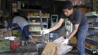 Workers clean the debris following Wednesday night's shooting outside a grocery store in Pattani province, southern Thailand, 2 May 2013