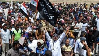 Masked Sunni protesters wave Islamist flags at an anti-government rally in Fallujah on 26 April