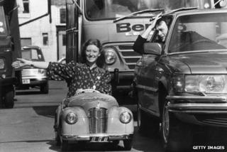 Blue Peter presenter Lesley Judd driving a toy car, 1978