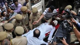 """Pakistani prisoner Sanaullah, an inmate of India""""s central Jammu jail that was attacked by Indian inmates at a prison, is carried from a hospital to an ambulance in Jammu on May 3, 2013, before being transferred to a hospital in Chandigarh for treatment"""
