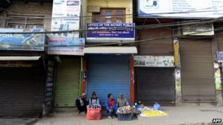 File photo: Street vendors sit on the sidewalk in front of closed shops in Nepal's capital, Kathmandu, 6 March 2013