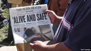 Man holds up a newspaper