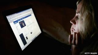 Teenager looks at Facebook