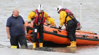 Man stuck in mud with lifeboat behind him
