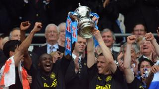 Wigan Athletic players lift the FA Cup.