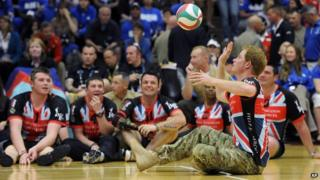 Prince Harry playing sitting volleyball.