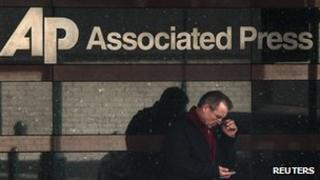 Man looks at his phone outside the offices of the Associated Press in Manhattan, New York (13 May 2013)