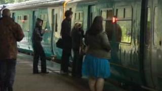 Rail travellers prepare to board a train