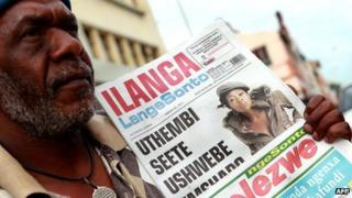 A man holds a copy of a Zulu language newspaper in Durban, South Africa (20 March 2011)