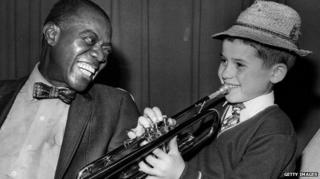 Louis Armstrong smiles as he hears Enrico Tomasso, nine, from Leeds play the trumpet in 1970