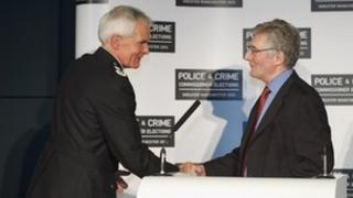 Tony Lloyd, Greater Manchester's PCC, shakes hands with chief constable Sir Peter Fahy