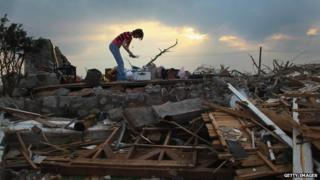 Woman stands on top of her demolished home in Joplin, Missouri