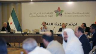 Head of the Syrian National Coalition for Opposition and Revolutionary Forces Moaz al-Khatib, rear-centre left, speaks during the group's meeting in Istanbul