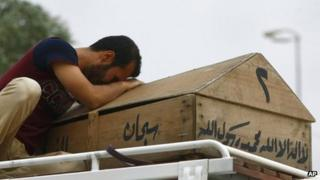 A man weeps over his daughter's coffin in the city of Najaf , 20 May