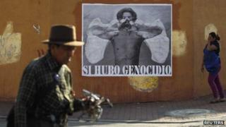 """Guatemalans pass a poster reading: """"Yes, there was a genocide"""" in Guatemala City on 15 May 2013"""