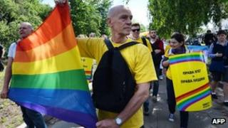 Activists carry a rainbow flag during a gay pride march in Kiev. Photo: 25 May 2013