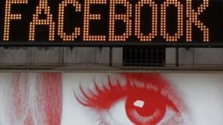 Facebook word on ticker screen over advert of woman