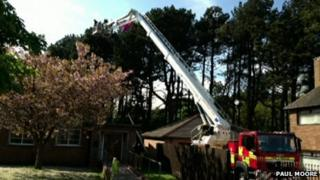 Fire engine platform being raised to rescue parachutist out of a tree