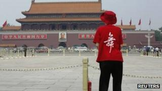 """A woman wearing a T-Shirt saying """"Dance"""" stands in Tiananmen Square (31 May 2013)"""