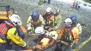 the girl being lifted into the hovercraft on a stretcher