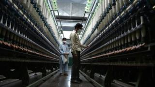 Pakistani workers carry out their daily work at the Kohinoor textiles factory in Rawalpind