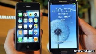 An Apple's iPhone 4s (L) and a Samsung's Galaxy S3 (R) at a mobile phone shop in Seoul