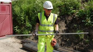 Senior site engineer Chris Williams holding a 3m (10ft) section of a soil nail