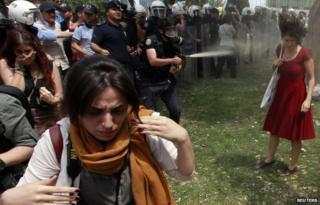 A Turkish riot policeman uses tear gas against Ceyda Sungur in Taksim Square