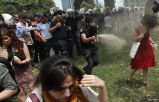 A Turkish riot policeman uses tear gas against Ceyda Sungur in Taksim Square