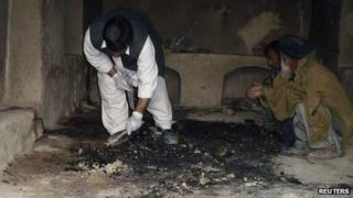 Afghan men investigate the site of a shooting in Kandahar province in March 2012
