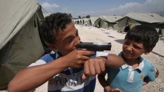 A boy plays with a gun at a refugee camp in Jordan