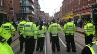Police in a line in front of protestors