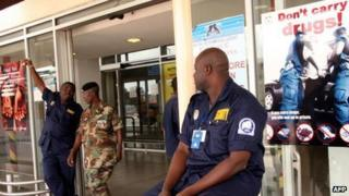 Security guards stand by anti-drug trafficking posters outside Kotoka International Airport, in Accra - 2007