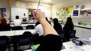 Schoolchildren raise their hands in a classroom as a teacher stands by a whiteboard