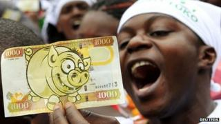 A protester displays a modified Kenyan bank note imprinted with an image of a pig in Nairobi during 11 June 2013