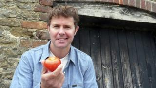 Stefan Gates holding a tomato