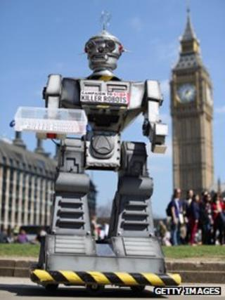 A mock 'killer robot' distributes promotional literature calling for a ban on fully autonomous weapons in Parliament Square