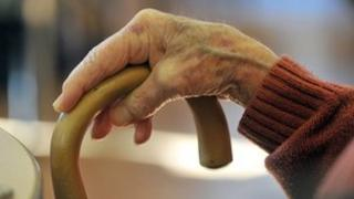 Elderly lady's hand on walking stick
