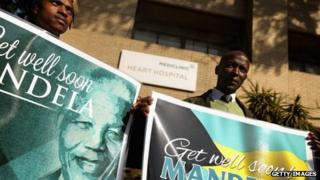 Well-wishers from South Africa and the Bahamas stand with signs outside the Mediclinic Heart Hospital where former South African President Nelson Mandela, 94, has spent the previous the week June 16, 2013 in Pretoria, South Africa.