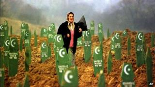 Woman walks through graves of Bosniaks reburied after being found in a mass grave, in Memici, 1999