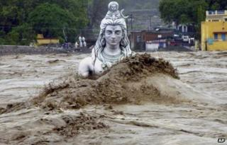 Flood waters gush around a giant statue of Lord Shiva in the holy city of Rishikesh in Uttarakhand state