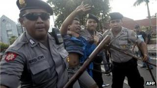 Indonesian police arrest a demonstrator following clashes at a protest over fuel price increase in Surabaya on June 21