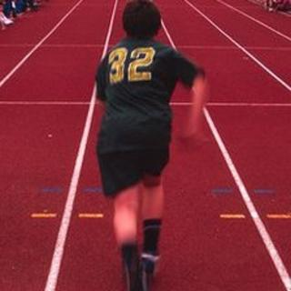A boy running a race at school sports day