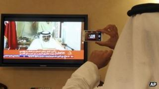 A man prepares to take a picture with his mobile photo of a televised address by Qatar's Emir Sheik Hamad bin Khalifa Al Thani