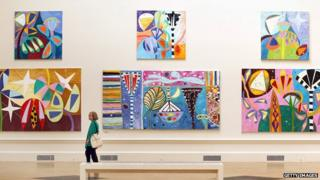 A visitor looks at paintings hanging at The Royal Academy Summer Exhibition