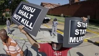 An anti-death penalty protester stands outside the the Texas Department of Criminal Justice Huntsville Unit (26 June 2013)