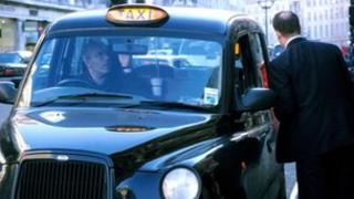 Man getting into a black taxi
