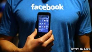 Facebook employee holds a mobile phone