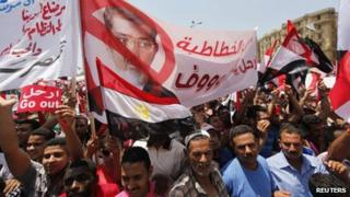 Protesters opposing Egyptian President Mohamed Morsi hold up a banner during a protest at Tahrir Square in Cairo