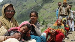 Stranded pilgrims wait for their turn to be evacuated in an Indian Air Force helicopter at Badrinath on 29 June 2013